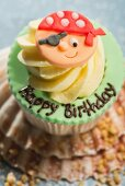 A cupcake decorated with a pirate for a birthday