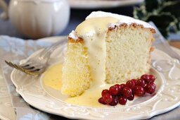 A slice of Angel Food Cake with zabaglione sauce and redcurrants