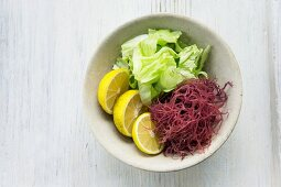 A bowl of iceberg lettuce, red seaweed and yuzu slices