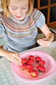 A girl decorating mini muffins in a kitchen