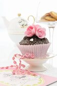 A cupcake decorated with pink sugar flowers for Valentine's Day
