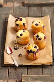 Blueberry muffins baked in glasses on a piece of baking paper