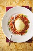 Turkey escalope with a mozzarella coating on a bed of tomato carpaccio