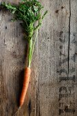 A single carrot on a wooden surface