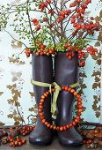 Wreath of rose hips tied to wellington boots filled with branches of rose hips