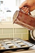 Yorkshire pudding batter being poured into a tin