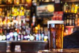 A pint of freshly drawn ale on the bar in a pub