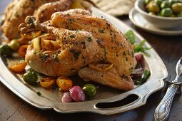 Two roast chickens with lemon, olives, onions and herbs