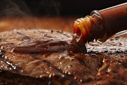 Steak sauce being poured onto a grilled steak