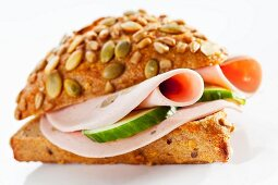 A pumpkin seed roll filled with mushroom mortadella and cucumber