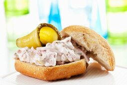 A bread roll filled with a creamy meat salad and gherkins