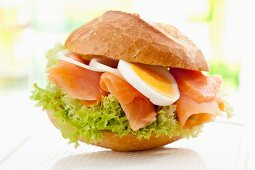 A bread roll filled with smoked salmon, egg and onions