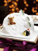 A ski slope cake with a reindeer and a penguin