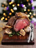 Sliced roast beef on a wooden board with garlic