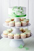 Vanilla cupcakes and a wedding cake decorated with green butterflies and sugar flowers on a cake stand