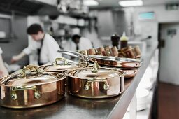 Copper pots in a restaurant kitchen with chefs working in the background