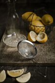 Lemon pips in a sieve and juiced and whole lemons