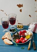 An appetiser platter with stuffed vine leaves and vegetables, white bread and red wine