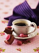 Marzipan sweets and chocolate-coated almonds with a cup of coffee