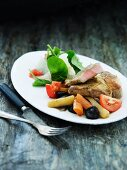 Beef steak with root vegetables, tomatoes and prunes