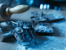 An arrangement of cookie cutters, a rolling pin and flour
