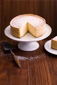 A cheesecake on a cake stand (sliced)