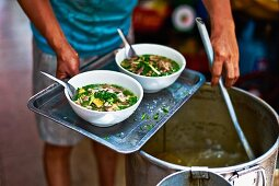 A man ladling pho ga (Vietnames chicken soup) from a vat into bowls