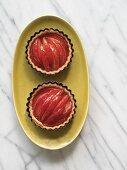Two gluten-free plum Tarts in ramekins on an oval plate