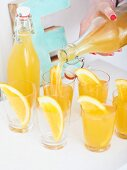Homemade orange and ginger lemonade being poured into glasses