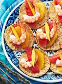 Mini blinis with orange, watermelon and prawns