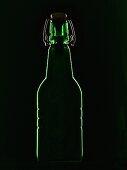 A green beer bottle with a flip-top lid backlit against a black background
