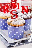 Vanilla and chocolate muffins in polka dot paper cases with red sugar letters