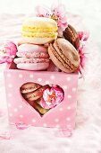Macaroons in a heart-shaped box with apple blossoms