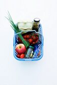 Eggs, chives, an apple and tomatoes in a shopping basket