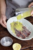 Sauce being poured over anchovies
