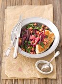 Warm chickpea salad with beetroot leaves and shallots served with grilled chicken breast
