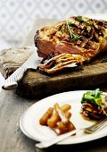 Crispy roast beef with a mustard crust on a chopping board, partially sliced