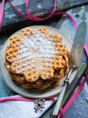 A stack of waffles with icing sugar