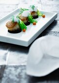 Fried scallops topped with foam served on a white rectangular plate