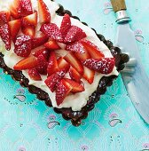A cake with chocolate glaze, vanilla cream and strawberries
