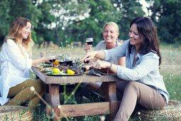 Three women eating a Provençal meal in a garden
