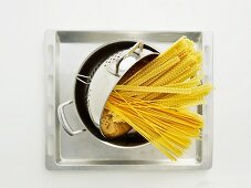 Pasta in a colander in a pot on a baking tray