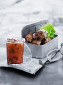 Chilly meatballs in a picnic tin with a dipping salsa
