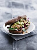 A wholemeal roll filled with salmon, avocado and radicchio