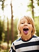 A boy in a forest sticking out his blue-coloured tongue