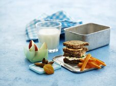 A lunchbox with wholemeal sandwiches, carrots, fruit and milk