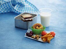 A sandwich, muffins, vegetables, grapes, almonds and milk for lunch