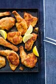 Roast chicken with lemon on a baking tray