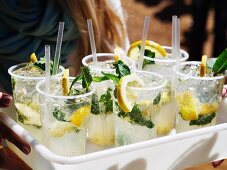 Ice cold lemonade with lemons and herbs in plastis cups (market in Pretoria, South Africa)