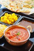 Chicken Tikka Masala with curried potatoes, rice, and lentils with naan bread (India)